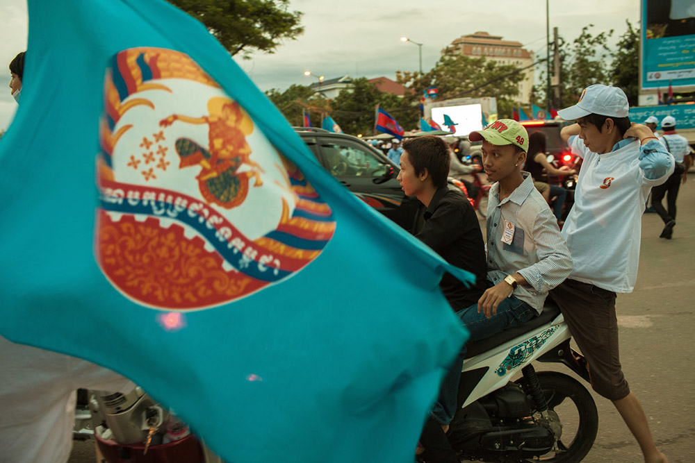 Members of the CPP's (Cambodia People's Party) Youth movement, jump on a motorbike for a parade through the streets of Phnom Penh. 06/07/2013 © Thomas Cristofoletti / Ruom