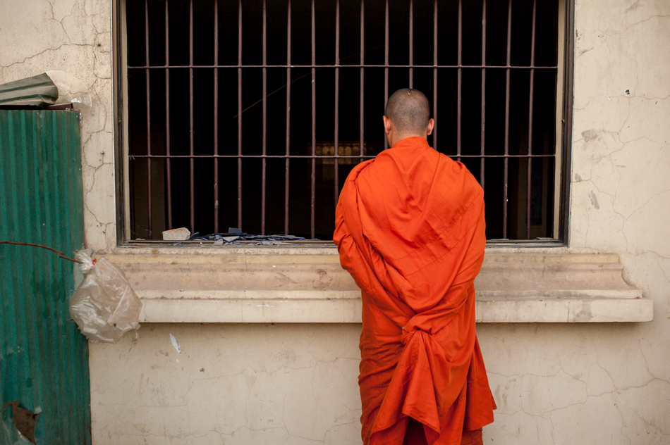 February 1, 2014 - Phnom Penh. A monk looks inside a medical clinic that was destroyed by protestors during clashes with police early in January. When clinic's doctor refused to help a wounded protestor, an angry mob forced entry, smashing and looting the interior. © Luc Forsyth / Ruom