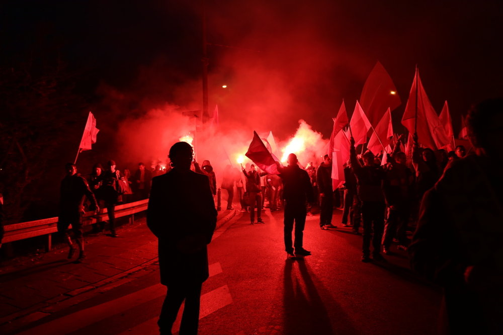 People taking part in the parade fire up red flares, minutes before violence erupts. © Marta Kasztelan