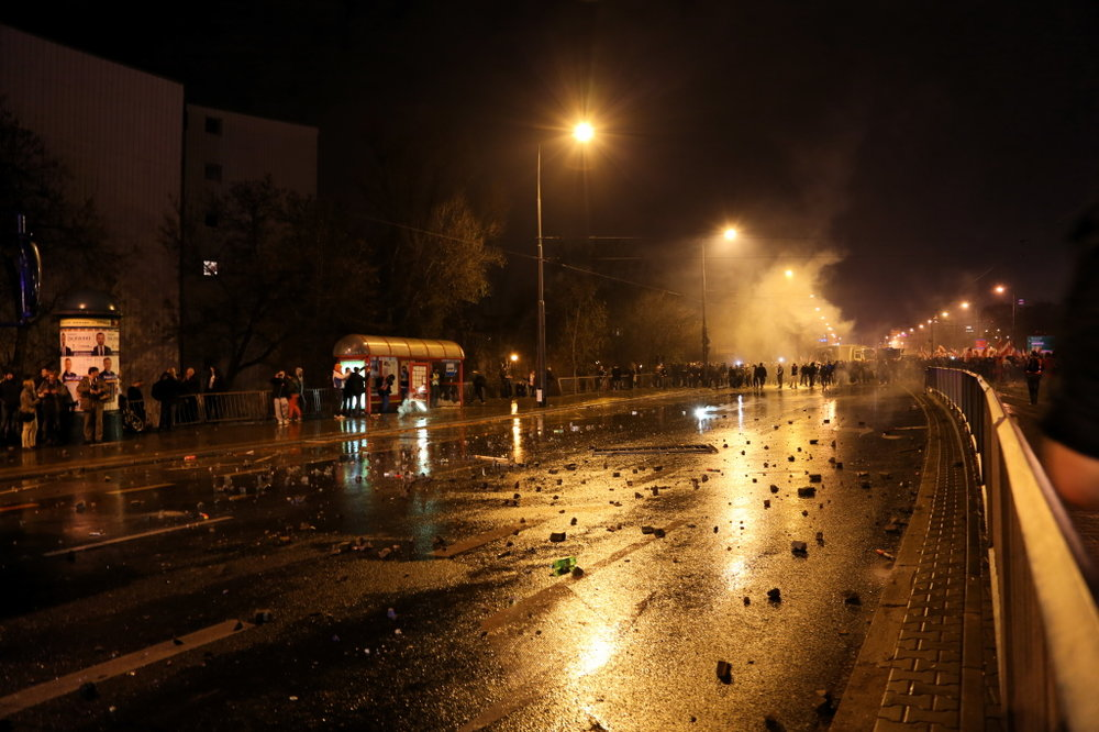 Cobble stone and bits of pavement lie on the road where the hooligans, standing in the back, clashed with the riot police. © Marta Kasztelan