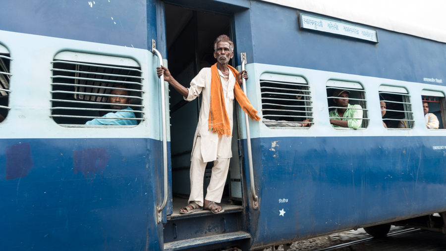July 18, 2016 - Bareilly, India. A man looks out from a passing train. © Nicolas Axelrod / Ruom