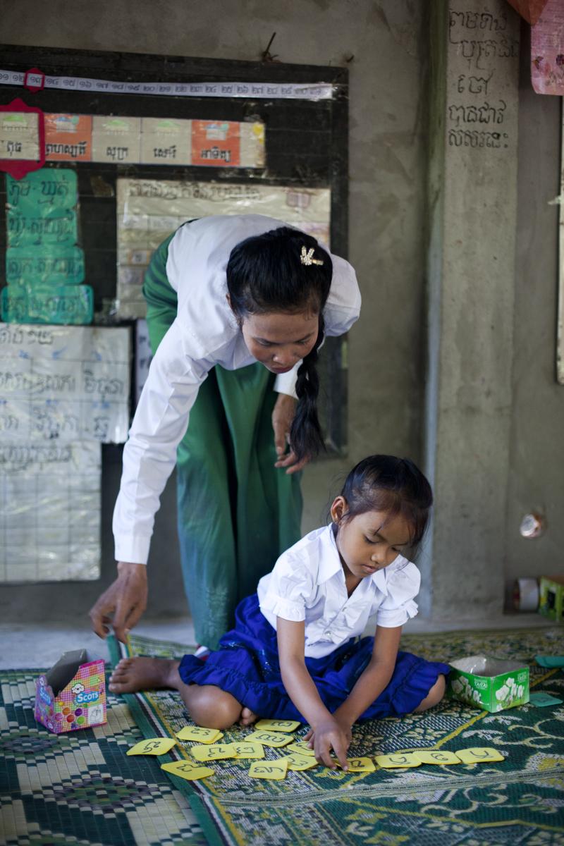 Volunteer teacher Heng Sokpheap (34) helps a child who attends the 7-9 am community pre-school. Khmout village. Svay Rieng
