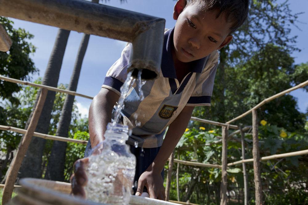 Hear Sopak (10) prepares a bottle for solar water disinfection (SODIS)  WASH, Krang Sleng Village, Prey Krasang Commune, Oudong district, Kampong Speu.