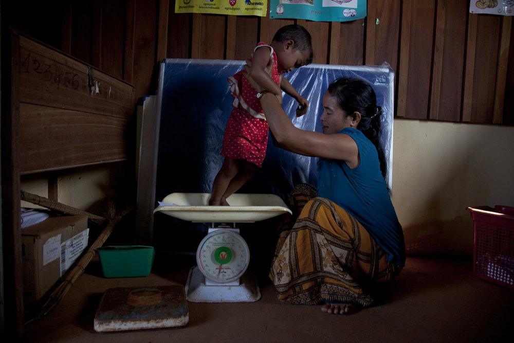 Pheap Jheune weighs her son Phea (2) at the Laoka Health Centre, Mondulkiri.