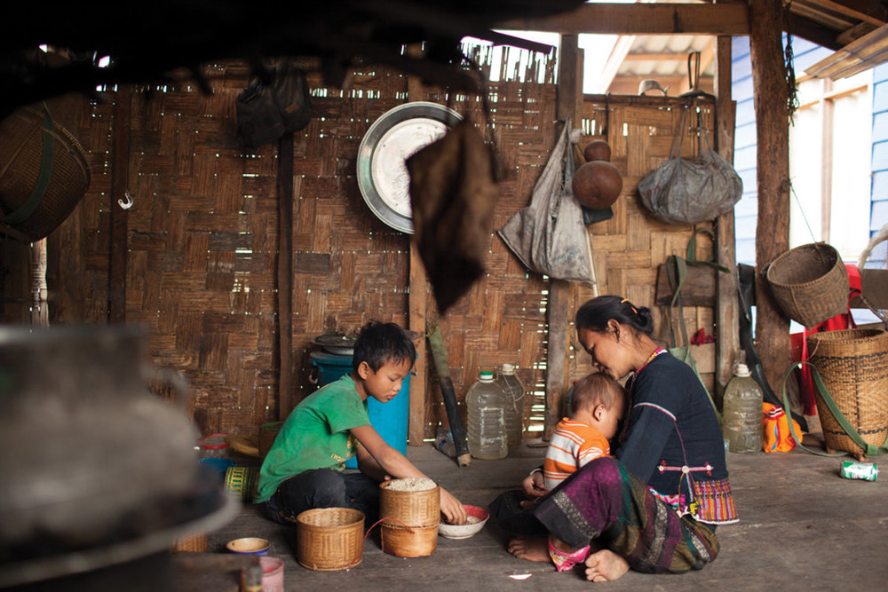 Jan. 18, 2013 - Savannakhet, Laos. Man Khleu (30) UXO victim and two of her children sit down for lunch in their home, Tam Louang village. � Nicolas Axelrod for HI