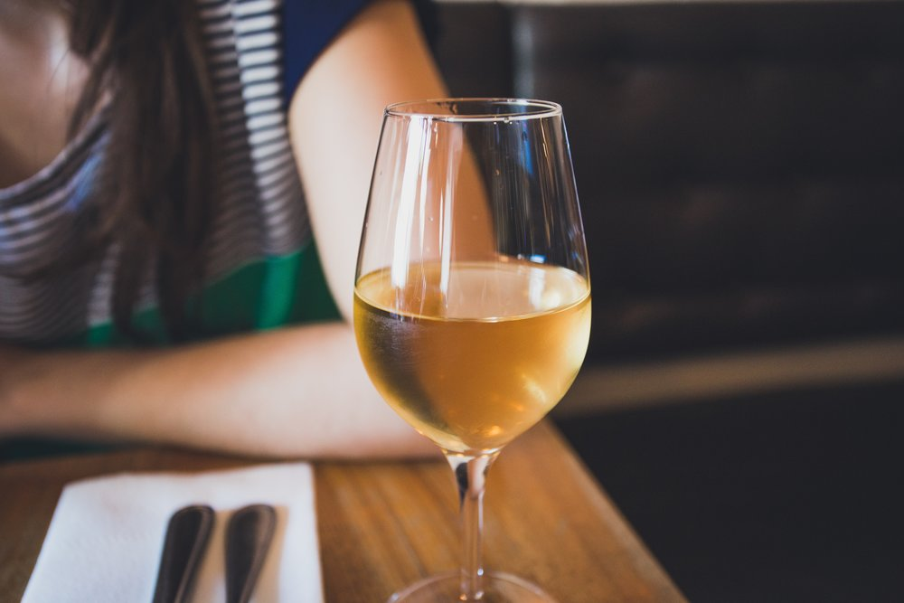 Woman sitting in restaurant with glass of white wine