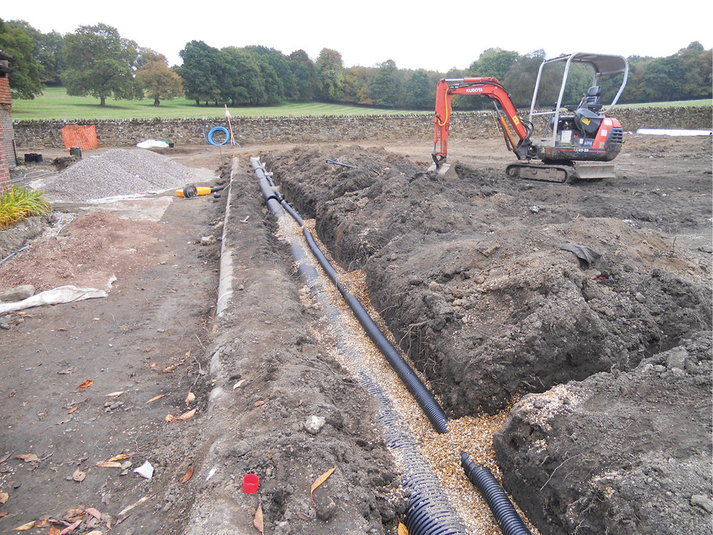 Installing a garden drainage system to ensure healthy grass growth.