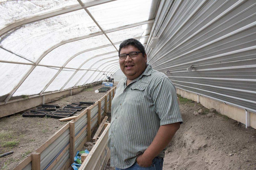 Food Sovereignty Program Coordinator at Thunder Valley, Ernest Weston, stands in a newly built green house on the Pine Ridge Reservation in South Dakota.