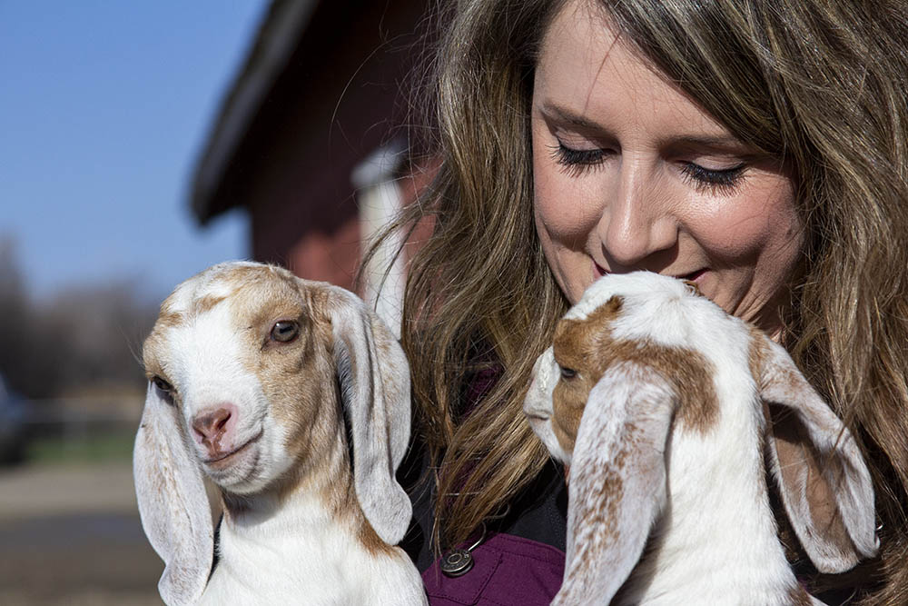 Sara snuggles with two goats at her home in Molt, Montana.