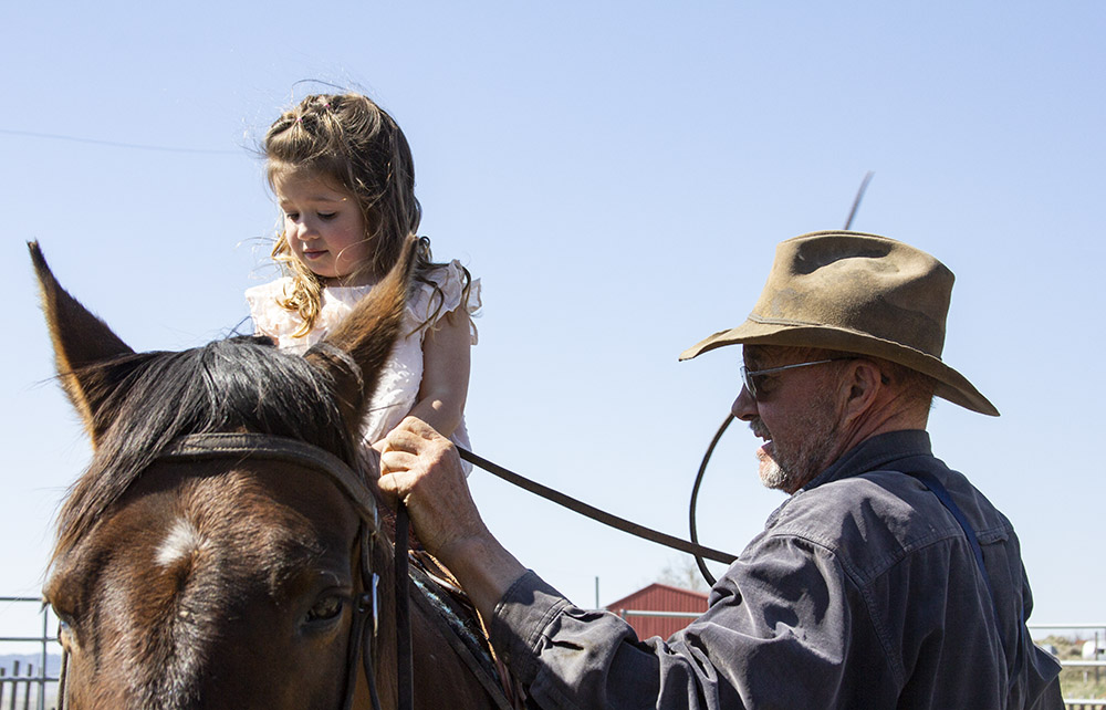 Stevie (left) on horseback next to her grandfather Steve.