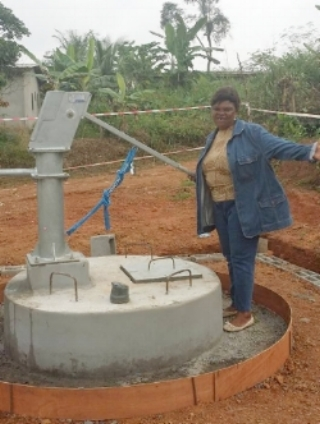 A Plant A Seed Volunteer poses with a newly built well in Sangmelima, Cameroon.