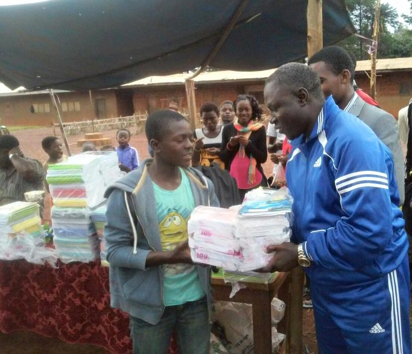A student accepts notebooks from a Youth Activities coach.