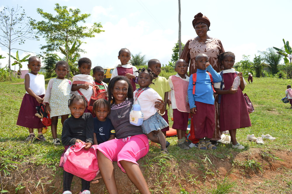 Plant A Seed Africa Founder, Ruth Akumbu, with students at Alfred & Sarah Bilingual Academy in Sangmelima, with school founder, Ma Hannah. Plant-A-Seed helped the Academy install a well for clean drinking water on campus. The well also serves the local community.
