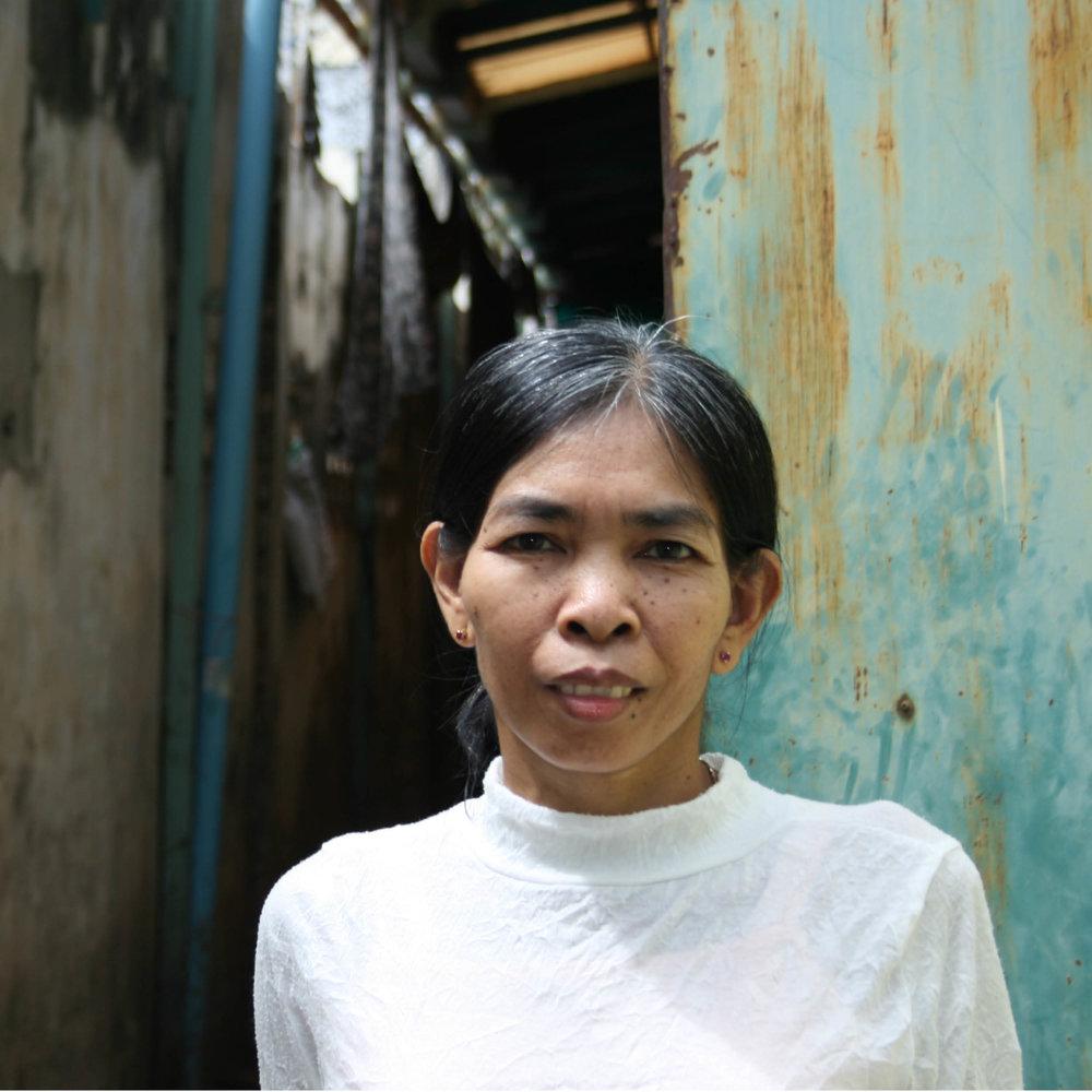 """NÄHERIN & TRAINERIN    HERKUNFT: Phnom Penh, Kambodscha ALTER: 59  ♥ FARBE: weiß   Ich heiße Khoun Sithat, Ich habe zwei Schwestern, bin single und ich bin in der Proving Kampong Chnang aufgewachsen. In meiner Freizeit schaue ich gerne fern.  Ich träume davon, ein eigenes, schönes Häuschen zu haben und immer genug Geld zu haben um ein gutes Leben zu leben. Diese beiden Dinge würden mich glücklich machen.  Für uns Kambodschaner ist Geld sehr wichtig - bei uns sagt man: """"Kein Geld, kein Leben.""""  Ich wünsche mir, dass mehr Leute auf der Welt Gutes tun indem sie unsere handgemachten Produkte kaufen, die wir körperlich behinderten Menschen in unserer Werkstätte anfertigen.  Ich mag meinen Job als Näherin, es ist ein sehr kreativer, aber ruhiger Job. Ich bringe auch hier in unserem Workshop den jüngeren Leuten das Schneidern bei. Es macht mir große Freude zu zu sehen, wie sie besser und besser werden."""