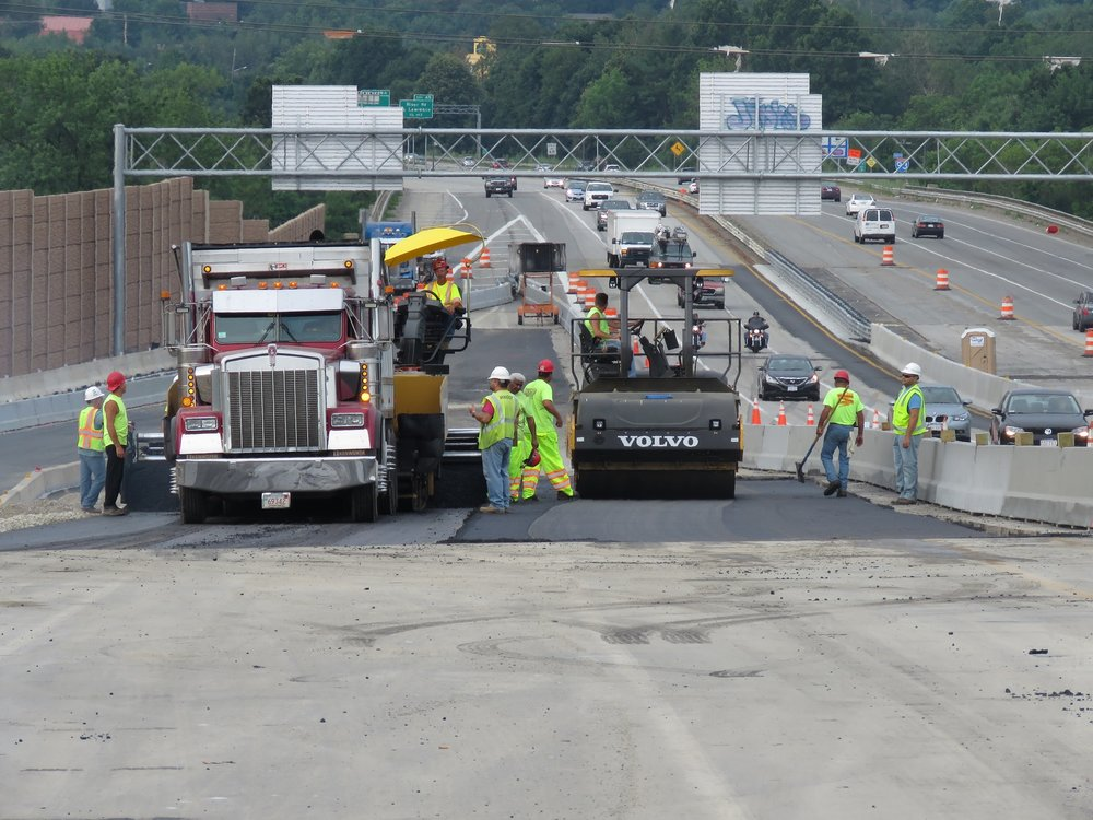 Construction workers repairing highway pavement.