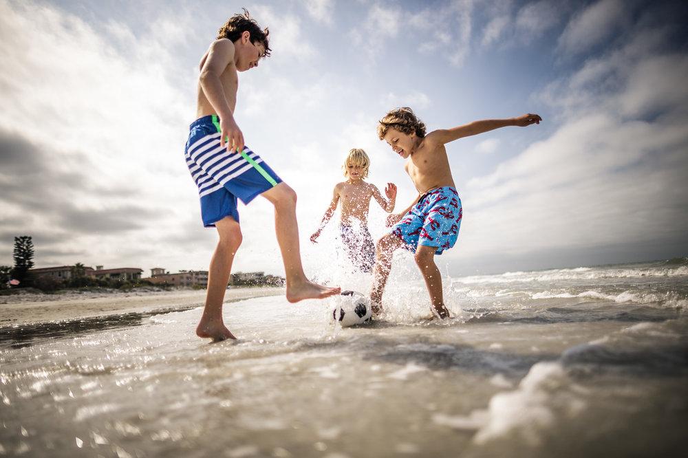 Three-Young Boys-Friends-Kicking-Soccer-ball-Shore-X2.jpg