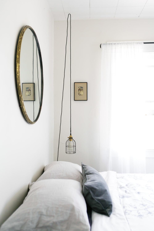 minimalist-bedroom-with-round-mirror-and-hanging-pendant-via-@citysage.jpg