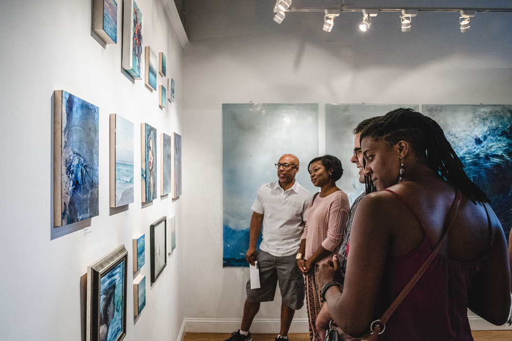 People looking at artwork on a gallery wall.