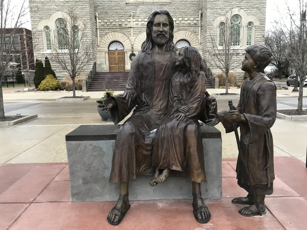 """""""Jesus and the Children"""" bronze is beautifully located directly in front of the Basilica of Saint Adalbert in a plaza at 654 Davis, NW, Grand Rapids, Michigan. Visitors are invited to sit on the statue next to Jesus."""