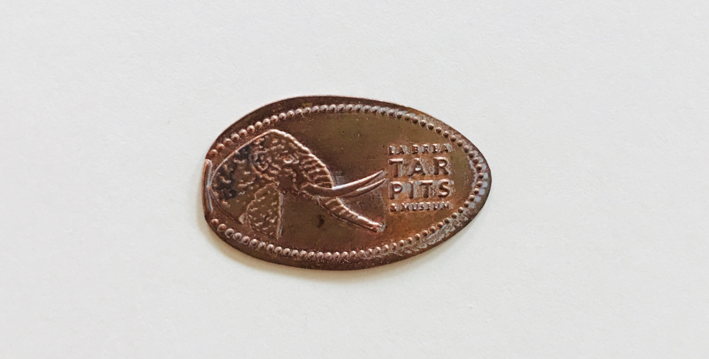A novelty coin, pressed from a 2016 United States one-cent coin (97.5% zinc, 2.5% copper) from the La Brea Tarpits Museum in Los Angeles, California.)
