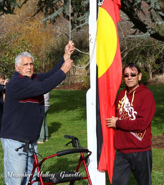 Uncle Viv Beeton and Hank Horton raise the aboriginal flag at Deloraine Cenotaph