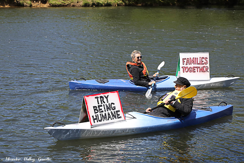 Margaret Tabor and John Phelps added their voices to a protest for refugees held on the Meander River.  Photo by Mike Moores
