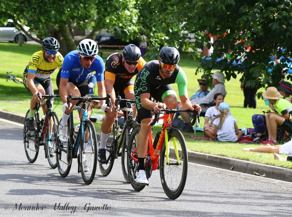 Competitors in the Masters Criterium power past the Village Green in Westbury on Boxing Day.