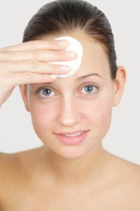 Young woman cleancing her face and applyting lotion. Skincare concept.