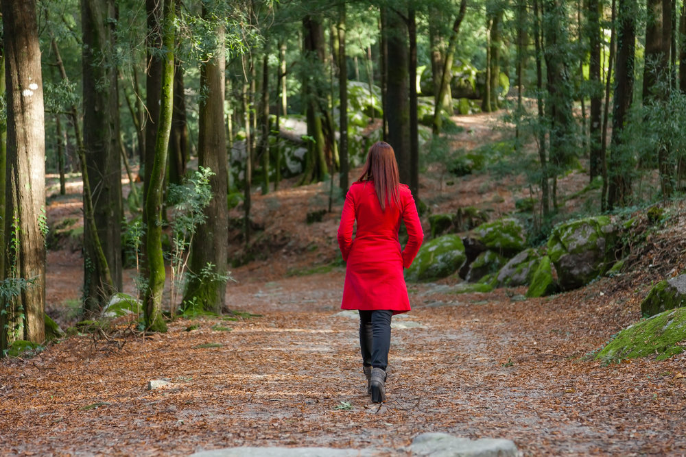 Young woman walking away alone on a forest path