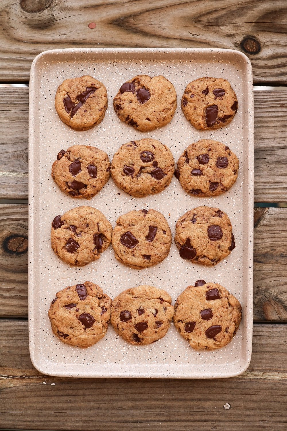 Chocolate Chip Cookies - INGREDIENTS:1 1/4 cup all purpose flour1/2 tsp salt1/4 tsp baking soda1/2 tsp baking powder2/3 cups coconut or brown sugar1/3 cup melted coconut oil1/4 cup warm water1/3 cup chopped chocolateINSTRUCTIONS:Preheat your oven to 350F. Whisk together the flour + salt + baking soda + baking powder and set aside. In a separate bowl, mix together your sugar + oil + warm water*. Add the wet mixture to the dry, and mix until fully incorporated - but don't over-mix! Add and fold in your chocolate. Line a large or two small baking sheet(s) with parchment paper, and scooping your cookie dough - scoop a Tablespoons' worth, and roll between your palms. Place the balls on the baking sheets and slightly flatten using your palm. Bake your cookies for 15 minutes - and enjoy.* make sure that your water is not cold, because cold water will Harden your melted coconut oil and the texture will be wrong. When first testing this recipe, it happened to me the first few times and then I realized it was the water.