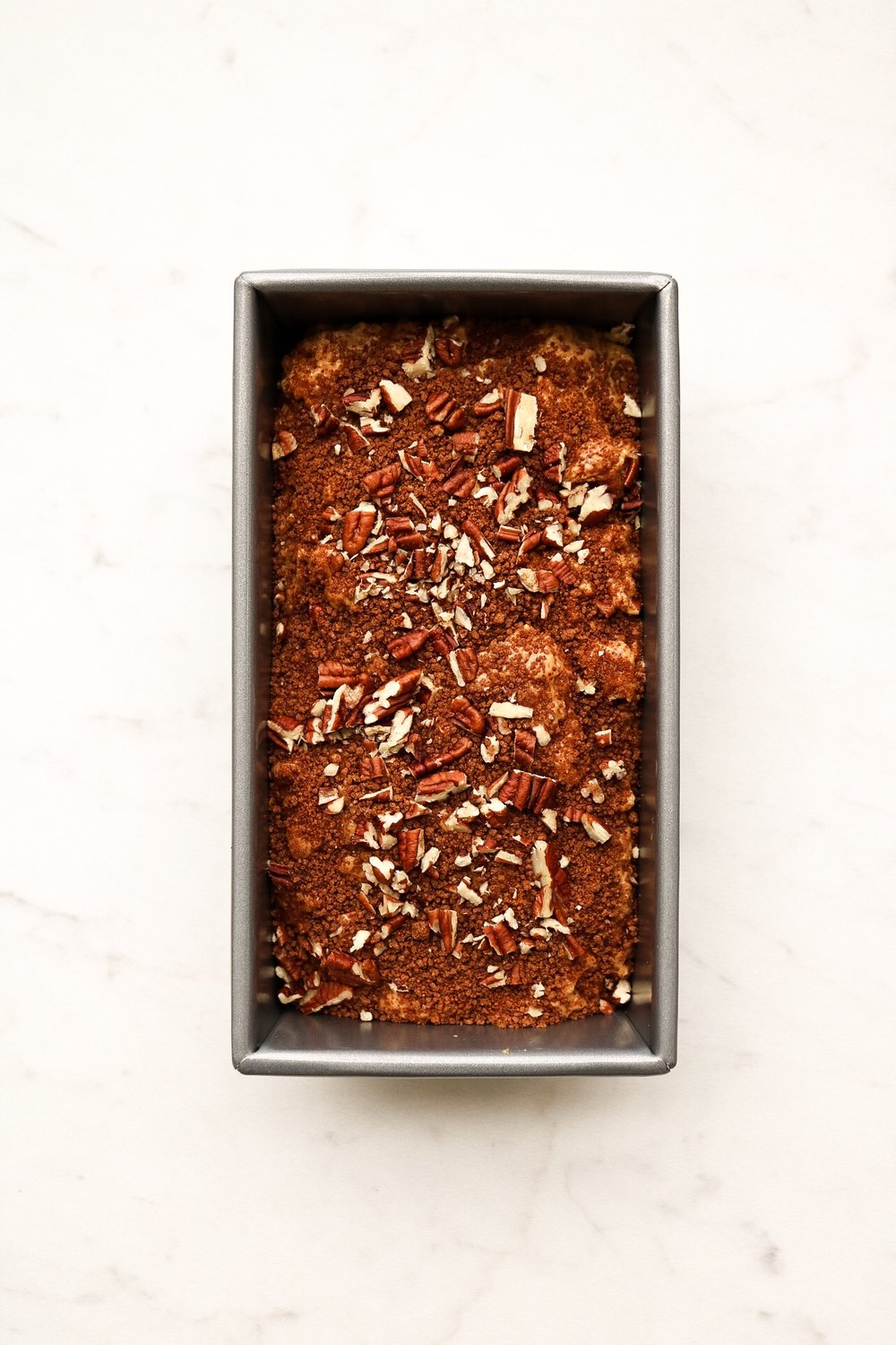 The batter after sprinkling the top with sugar + cinnamon + more pecans