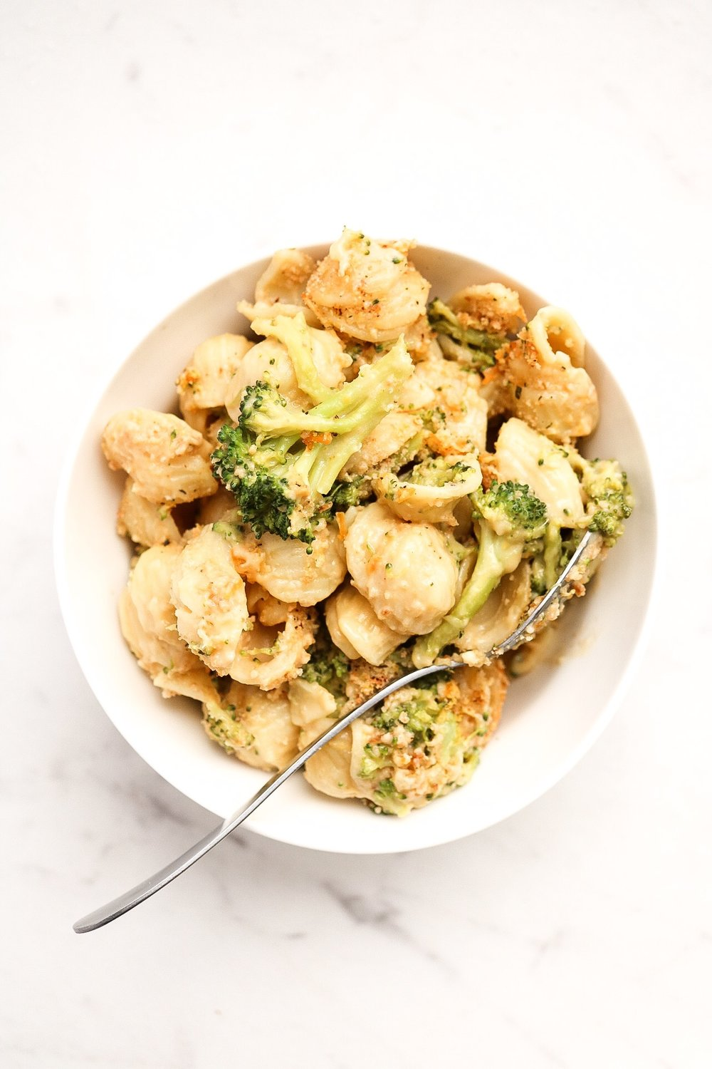 Broccoli Mac & Cheese - INGREDIENTS:3 cups pasta1 head broccoli1 Tbsp oil2 Tbsp all purpose flour1 cup plant milk1/2 cup vegan shredded cheese1/3 cup Bob's Red Mill nutritional yeast1 tsp salt1/4 cup breadcrumbsINSTRUCTIONS:Boil your pasta and broccoli until it's cooked about 3/4 of the way, and set aside. Preheat your oven to 400F. In a saucepan, add the oil and flour and allow to cook on medium heat for about a minute. This is your roux - the oil and flour will form into a paste and become golden, creating a nutty aroma. Slowly begin adding in the milk, and stirring as you do so. Once all of the milk is incorporated, allow the mix to come to a boil. Then, add in the salt, vegan cheese, and nutritional yeast. Once the sauce has thickened a bit and everything is melted, add in the broccoli and pasta and stir. Add this mixture to an oven safe pan, sprinkling your breadcrumbs on top, along with some extra vegan cheese and nutritional yeast. Bake the pasta for about 20 minutes - you can broil the top for the last few minutes for a nice golden color.