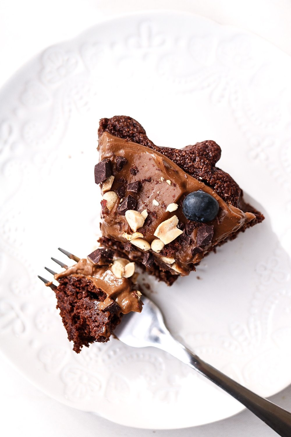 Date-Sweetened Chocolate Cake - CAKE INGREDIENTS:1 cup dates1 1/4 cup water1 Tbsp baking powder1/2 tsp salt1/3 cup cacao powder1 cup all purpose or spelt flour1/2 bar Alter Eco 90% dark chocolate - choppedFROSTING INGREDIENTS:1 ripe avocado1/4 cup plant milk2-3 Tbsp maple syrup2 Tbsp cacao powderINSTRUCTIONS:Preheat your oven to 350F. Line a cake pan with parchment paper and set aside. In a food processor, blend together the dates and water. Add in the remaining cake ingredients, except for the chopped chocolate, and pour the batter into the cake pan. Bake the cake for about 30 minutes, or until a toothpick comes out clean with you poke it. While the cake is cooling, blend together the frosting ingredients in a food processor until smooth.