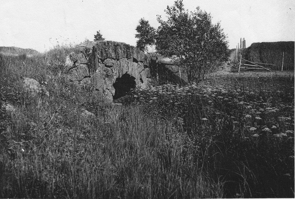 """""""Bergkvistabrona"""" fotograferad från väster mot Kivenäbben. Vägen österut i bakgrunden. Bliden tagen före 1930-talet. Då byggdes den om och valvet ersattes med en flat bro. När vägen sedan byggdes 1961 sprängdes den gamla bron bort helt. Samtidigt breddades vägen varvid en del av tomterna från de två stugorna försvann. När bron på bilden byggdes är okänt. Men vägen har alltid haft denna sträckning."""