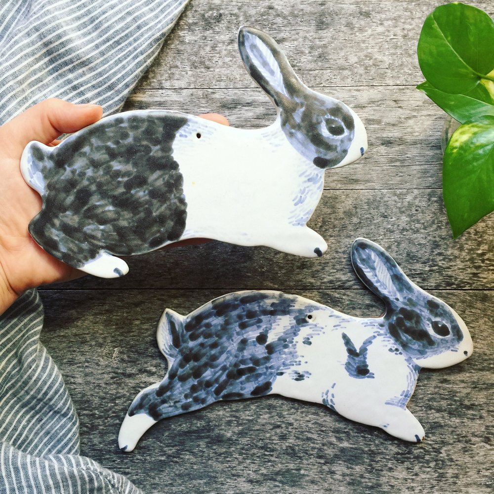Ceramic wall hanging portraits of pet rabbits Porkbun and Oliver.