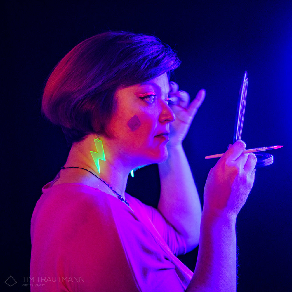 A woman is applying face paint in front of a UV light.