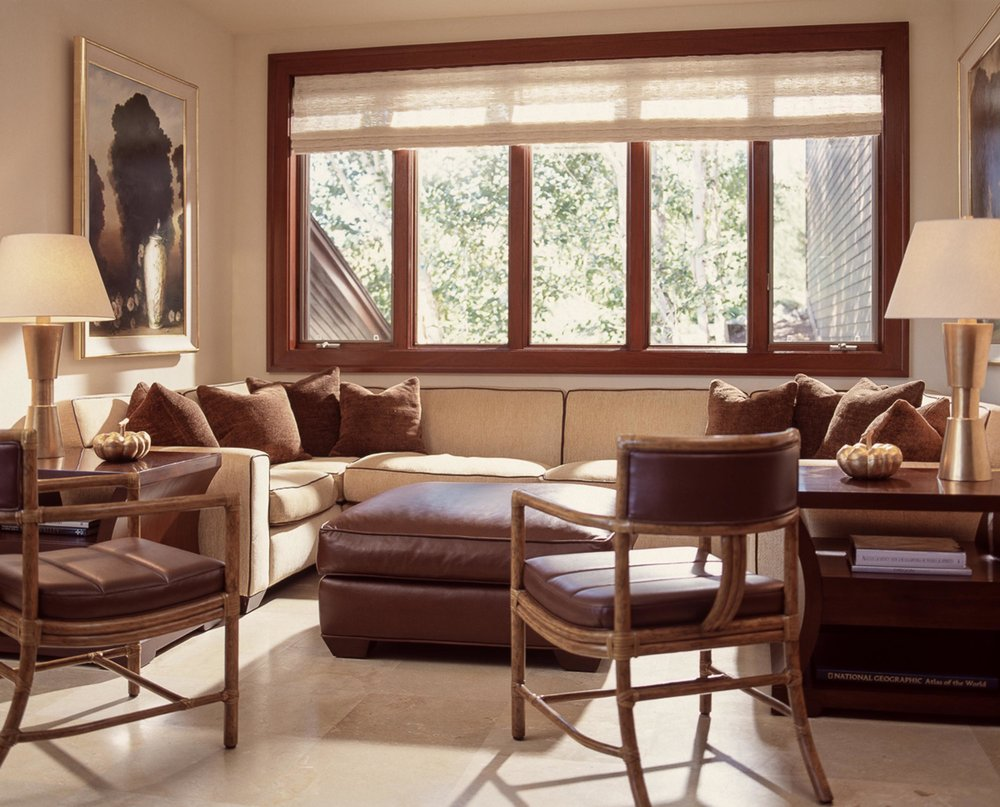Living room with sofa, ottoman, and wooden window
