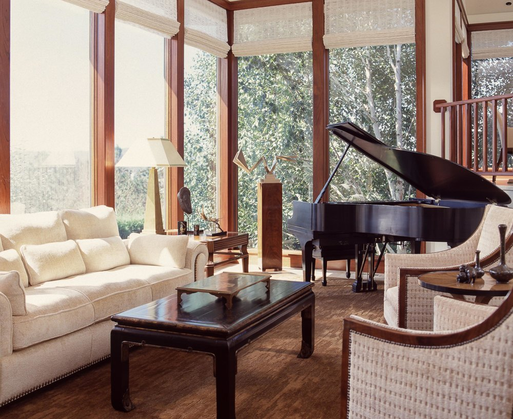 Modern living room with white sofa, wooden center table and a piano