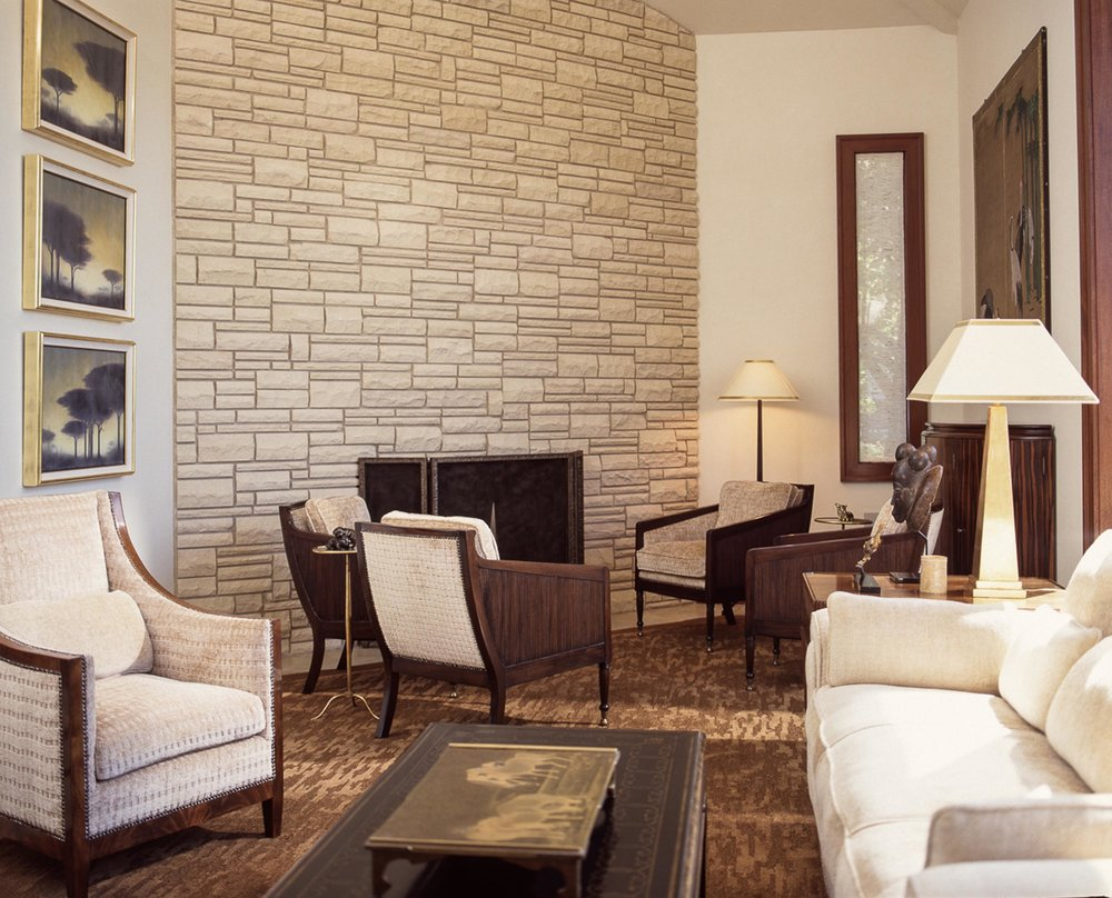Living room with white painted and brick wall with sofa and center table and frames