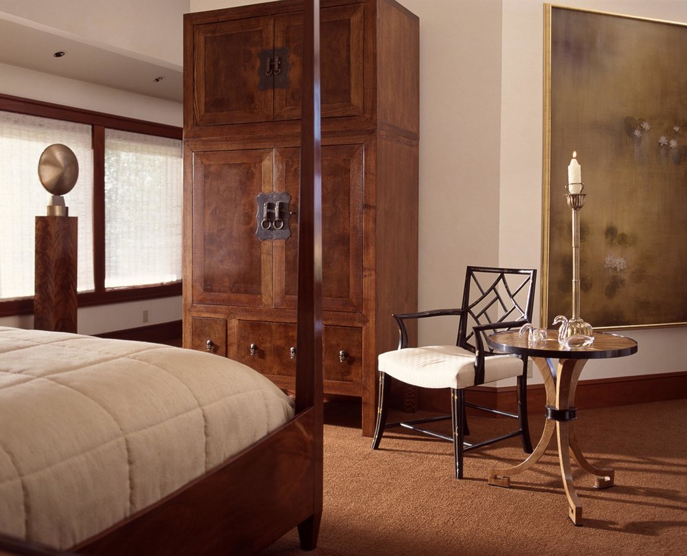 House bedroom with wooden cabinet, round table with chair and wooden bed
