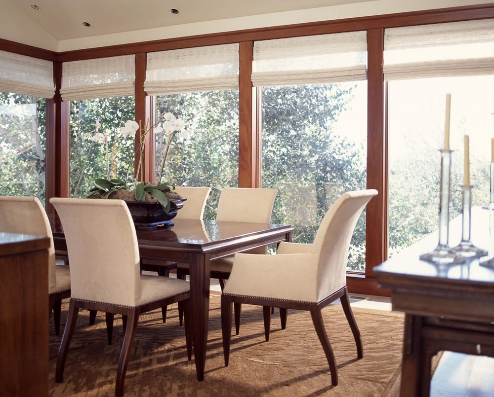 Dining room with wooden table, chairs and large glass windows