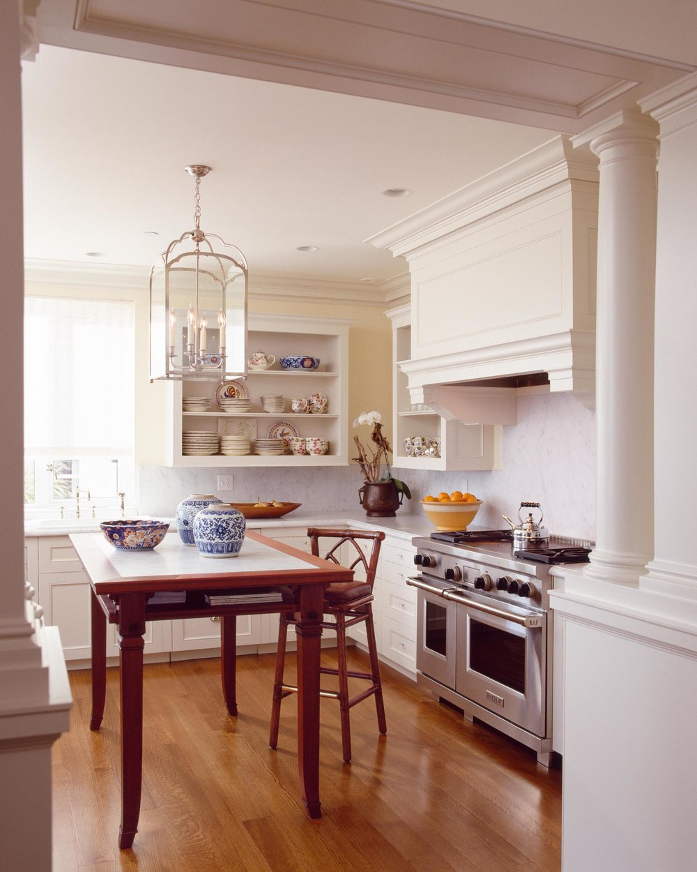 Kitchen with hardwood floor, table, chairs and exhaust hood