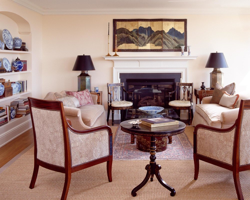 Living room with sofa, armchairs, round table, fireplace, table lamps and a large carpet