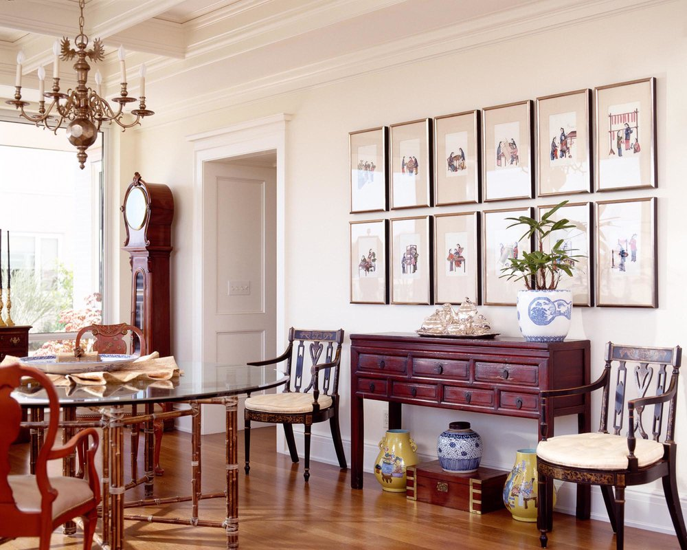 House interior with frames on wall, wooden chairs, chandelier and vintage clock