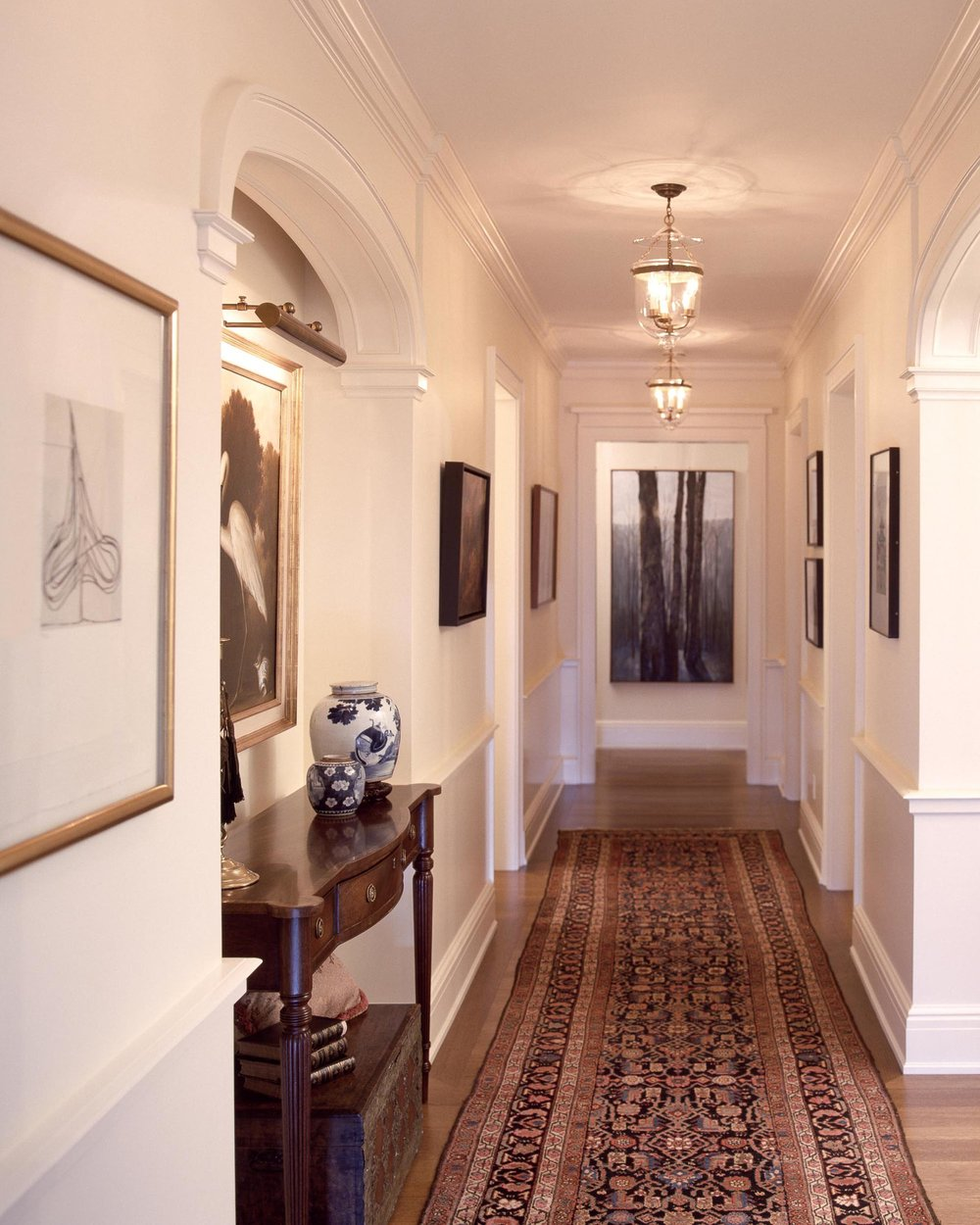 Hallway with carpet, frames on the wall, wooden table and vases on the top