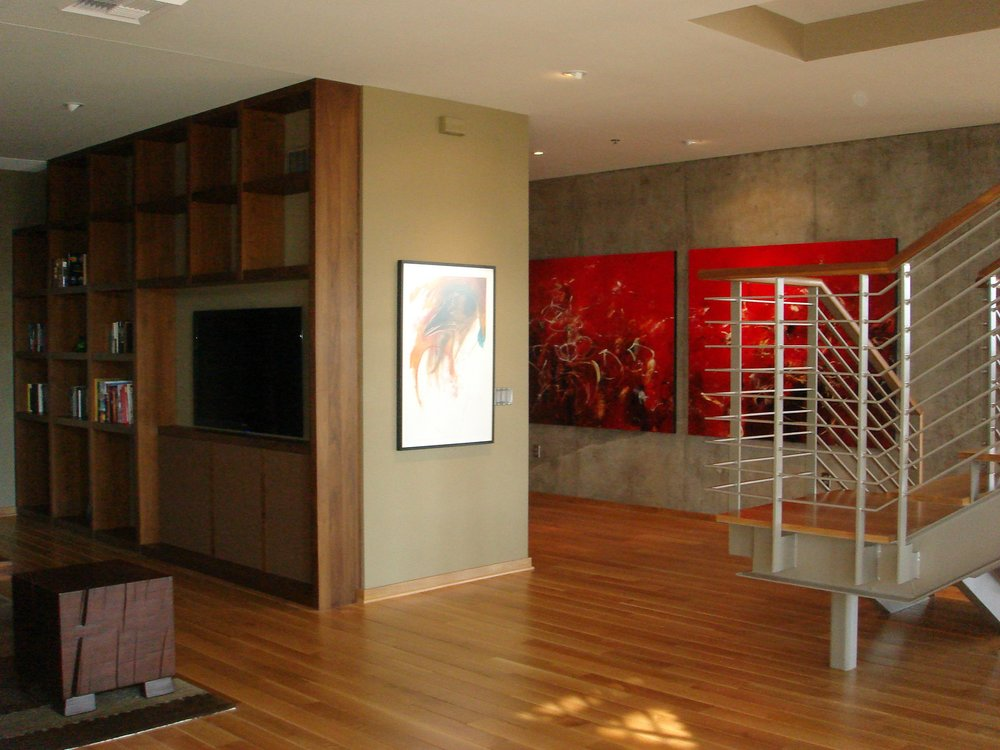 Modern house with hardwood floor, staircase and frames on wall