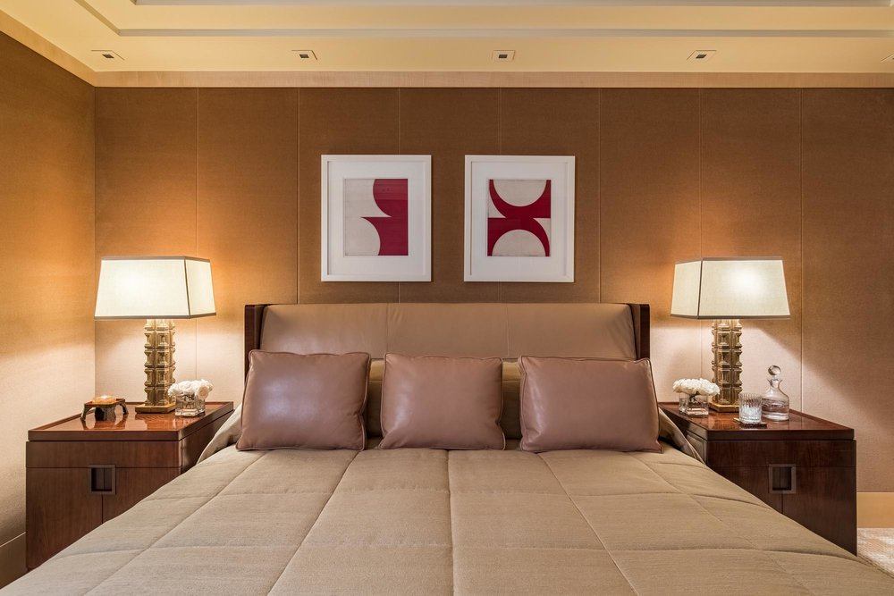 Bedroom interior with bed and wooden bed tables with lamp, and frames