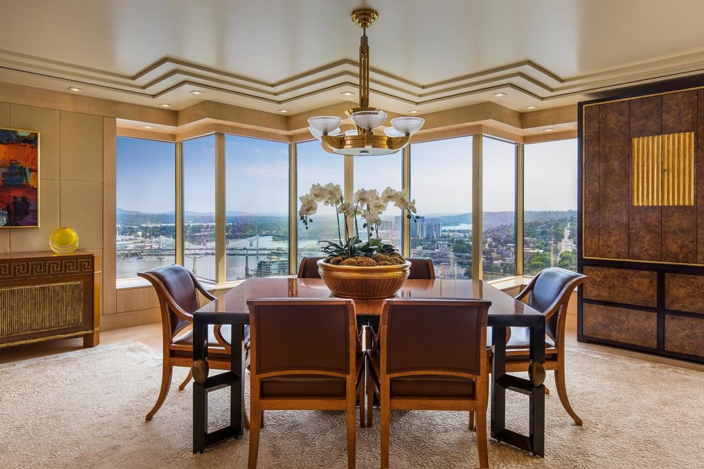 Dining room with table and chairs and a large window with city view