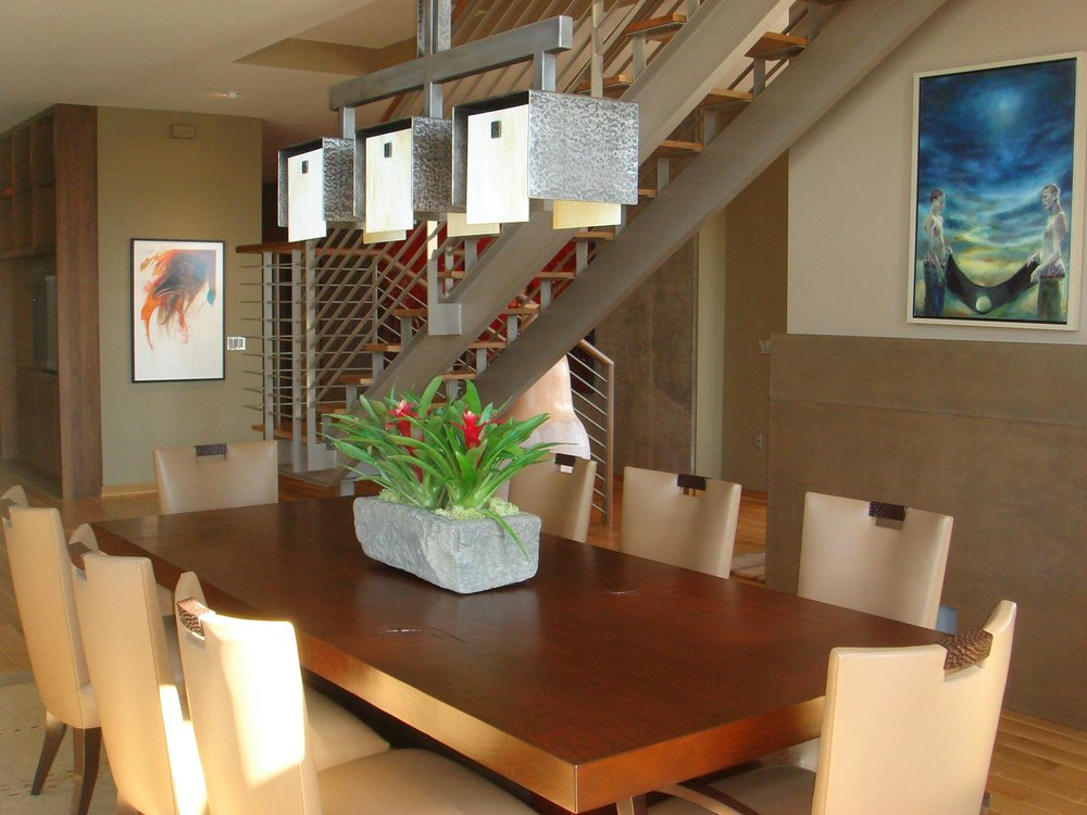 Wooden dining table with plant on top, chair and staircase