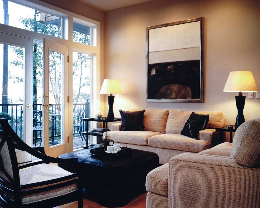 Living room with sofa, table lamps, frame on wall and a glass door